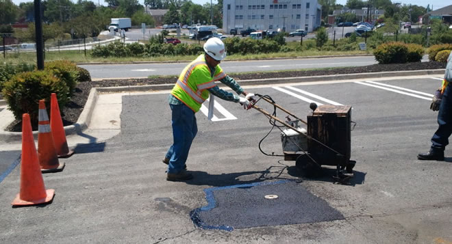 Applying crack fill around asphalt patch in Falls Church